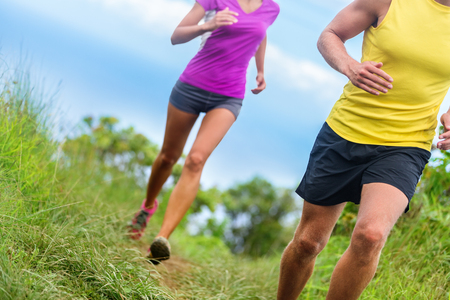 activewear: Fitness athletes trail running - athletic legs closeup lower body crop of man and woman working out. Sports people jogging in fast motion marathon race training on a nature path in shorts activewear.