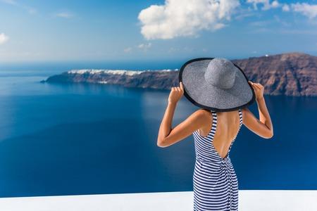 Europa zomervakantie reisbestemming luxe leven vrouw kijken naar weergave van de Middellandse Zee en het eiland Santorini Oia dorp. Elegante toeristische dame in de mode terug jurk en floppy zonnehoed.