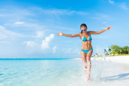 Vrijheid onbezorgd meisje opspattend water met plezier op tropische reizen ontsnapping vakantiebestemming strandvakantie. Speelse vrouw met abs slanke bikini lichaam ontspannen gevoel vrij. Stockfoto