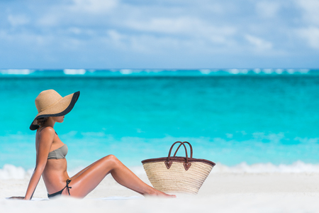 Bikini woman beach vacation sun tanning relaxing on beach. Suntan concept. Unrecognizable female adult enjoying the sunshine with straw hat sunbathing under the tropical sun on Caribbean vacation. Stock Photo