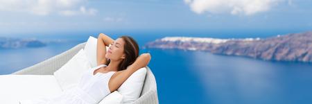 Entspannende Frau auf Outdoor-Daybed Gartenmöbel Schlaf Aussicht genießen von Mittelmeer Europa Reiseziel. Asiatisches Mädchen auf Kissen liegend träumen sorglos glücklich. Luxus-Haus leben.