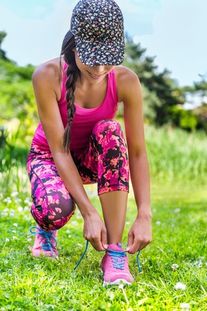 activewear: Cute sporty runner girl in fashion activewear wearing floral cap and pink leggings outfit getting ready for jogging tying laces running shoes on grass park. Fitness woman living active lifestyle.