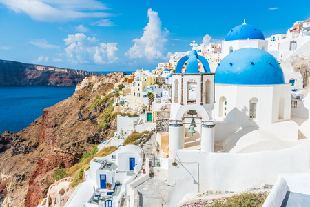 Greece famous touristic travel destination Santorini greek island. Three blue domes. Popular summer luxury vacation Europe cruise stop. Streets of European white village with the mediterranean sea. Фото со стока