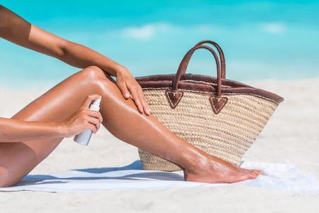 Sonnenschutz Sonnenspray von Hautpflege-Produkt Nahaufnahme der Frau auf die Beine Gerben Öl setzen. Hand hält Sunblocker oder Mückenschutz Flasche auf den Körper sprühen Sonnenbaden am Strand Sommerurlaub.