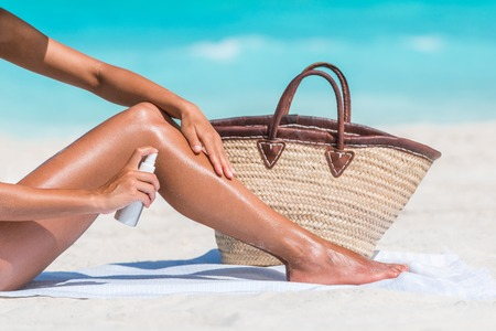 Sunscreen suntan lotion spray skincare product closeup of woman putting tanning oil on legs. Hand holding sunblock or mosquito repellent bottle spraying on body sunbathing at beach summer vacation. Stock Photo