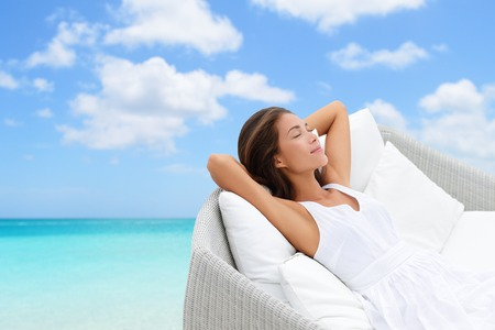 laid back: Sleeping woman relaxing lounging on white outdoor sofa day bed lounger on beach ocean background. Asian girl lying down laid back on pillows dreaming or enjoying the sun carefree happy. Home living.