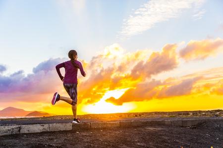 Atleet trailrunning silhouet van een vrouwelijke agent op zonsondergang weg zonsopgang. Cardio-fitness vrouw opleiding voor marathon race. Actieve gezonde levensstijl in de zomer de natuur buiten. Life uitdaging concept. Stockfoto