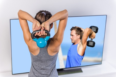 working at home: Fitness at home woman working out watching tv. Back of a young sporty girl following workout videos online on smart television, lifting kettlebell toning arms and shoulders exercising triceps. Stock Photo