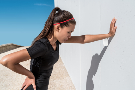 Tired athlete runner exhausted of cardio workout breathing hard after difficult exercise. Asian fitness woman running sweating of heat exhaustion leaning on wall of muscle back pain or cramps.