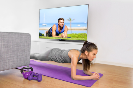 'flat stomach': Living room fitness workout - girl doing plank exercises to exercise core at home. Young Asian woman training muscles in front of the TV as part of a healthy lifestyle without going to the gym.