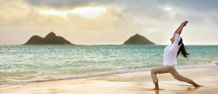 Yoga vrouw mediteren in krijger I stelt bij Hawaiiaanse strand tijdens mooie ochtend zonsopgang tegen Lanikai de bergen van Hawaii landmark. Banner panoramisch gewas voor reclame.