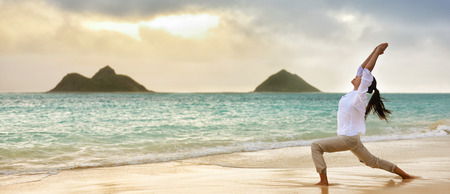 Yoga woman meditating in warrior I pose at hawaiian beach during beautiful morning sunrise against Lanikais mountains Hawaii landmark . Banner panoramic crop for advertisement. Stock Photo