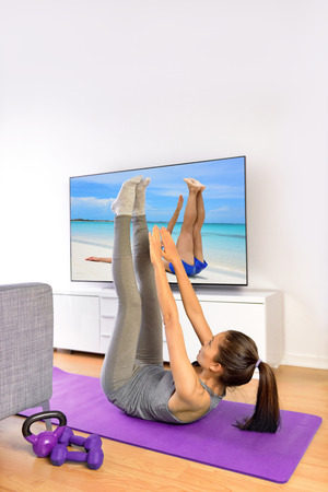 flat stomach: Home fitness ab workout in front of television. Girl doing toe touch crunch exercises to train upper abs for a flat stomach while watching a nature TV show or training program living a healthy life.