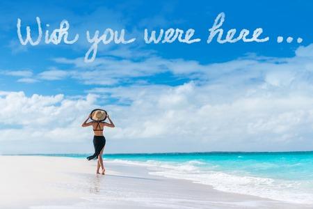 Ojalá estuvieras aquí nubes mensaje escrito en el cielo por encima de la mujer que camina en la playa vacaciones Viajes de lujo destino del Caribe. Turista que se relaja en vacaciones de verano en el complejo. postal dicho popular. Foto de archivo