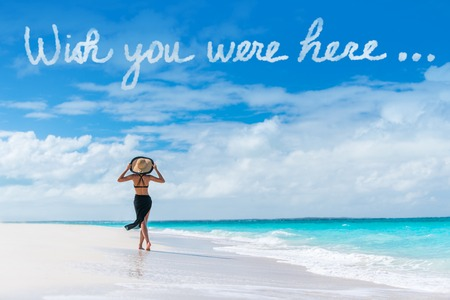 Wish you were here cloud message written in sky above woman walking on beach vacation Luxury travel Caribbean destination. Tourist relaxing on summer holiday at resort. Popular saying postcard. Stock Photo