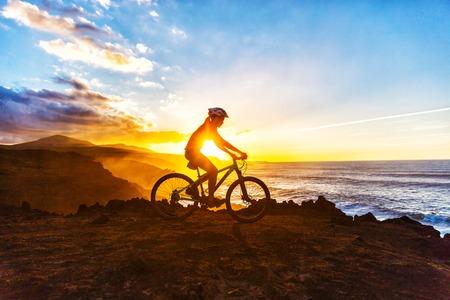 Mountainbiken MTB fietser vrouw fietsen op fietspad op kust bij zonsondergang. Persoon op de fiets door de zee in sportkleding met de fiets te genieten van een gezonde actieve leefstijl in de prachtige natuur.