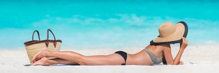 traje de baño: Mujer de la playa de vacaciones de verano de relax tomando el sol en la arena blanca del Caribe y el océano turquesa. muchacha turística joven tumbado en la toalla por el mar que lleva bikini y el sol sombrero de disfrutar de unas vacaciones de verano de viaje. Foto de archivo