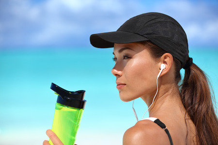 earbuds: Healthy sporty Asian runner woman running on beach drinking water bottle listening to music with earbuds and smartphone wearing sun cap for solar protection during summer. Active living. Stock Photo