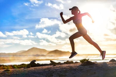 Atleet loper pad draait op de zomer strand. Fit lichaam silhouet van sport vrouw in sportkleding cap sprinten met energie en beweging in de natuur buitenshuis training cardio workout met jogging oefening. Stockfoto