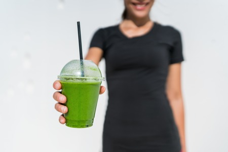 go: Green smoothie cup waitress woman serving drink at juice bar or cafe. Closeup of plastic take-away disposable container for restaurant business, person holding for healthy eating diet weight loss.