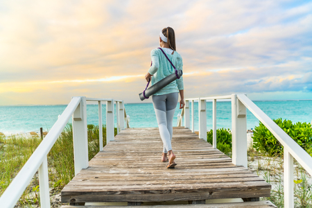 activewear: Fitness woman walking with yoga mat on beach going to outdoor meditation class at sunset. Back view of fit athlete in activewear fashion leggings and turquoise hoodie. Healthy active lifestyle.
