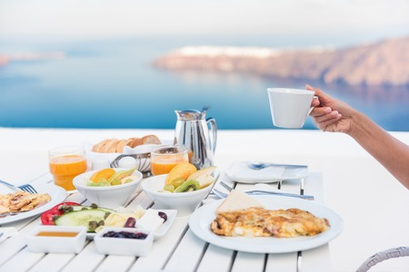 omelette: Morning person drinking coffee cup at breakfast table with mediterranean sea view. Woman eating at restaurant outside terrace patio on Santorini, Greece, Europe destination summer vacation.