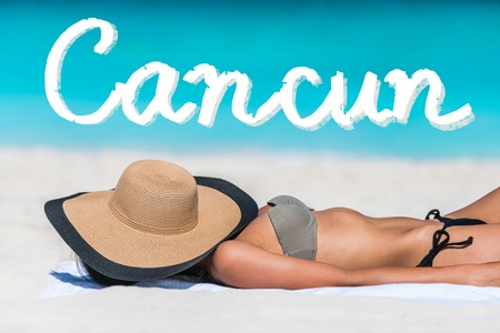 girl lying: Cancun, Mexico beach travel bikini suntan woman sleeping relaxing covering face with straw hat doing siesta. CANCUN text written in turquoise ocean copyspace above. Summer and sun vacation holidays.