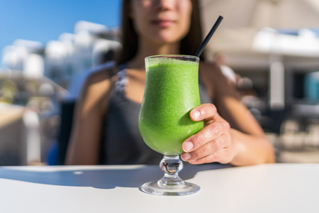cleanse: Healthy juicing lifestyle trend woman drinking green spinach juice smoothie cup at restaurant table. Unrecognizable person holding glass of fresh vegetables blend for a vegetarian diet detox cleanse .