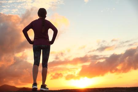 Donna attiva che guarda avanti al tramonto il cielo per la sfida della vita. Runner atleta si prepara per la scelta raggiungimento Trail Run pensiero obiettivo e la felicità. Persona di sesso femminile che vive lo sport stile di vita sano. Archivio Fotografico