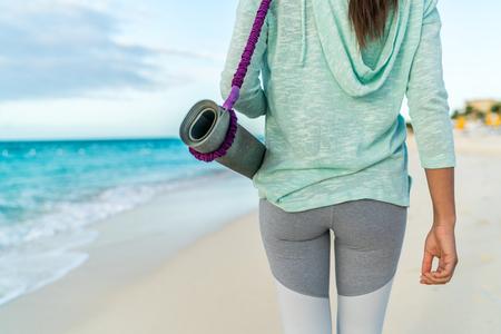 Fitness vrouw die yoga mat met riem op het strand gaan klasse training. Close-up van sportartikelen, achteraanzicht van fit atleet in activewear tonen mode leggings en turquoise hoodie. Stockfoto
