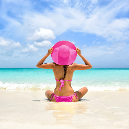 Perfect paradise summer vacation happiness carefree happy woman relaxing sitting in sand enjoying tropical beach destination. Back view of bikini girl holding pink straw hat on Caribbean holiday. Banco de Imagens
