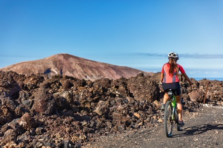 ecotourism: Mountain biking woman MTB cyclist cycling on nature volcano volcanic trail on vacation travel against mountains. Tourist doing sports activity during summer holidays. Leisure tourism, ecotourism. Stock Photo