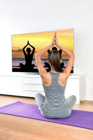 meditation room: Woman watching TV yoga meditation fitness at home. Fit girl doing easy pose relaxation exercises following TV show online workout video with arms raised sitting on the floor of the living room.