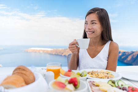 아침에 아침 식사 테이블에 뜨거운 음료를 마시는 아시아 여자. 이아 산토리니 섬, 그리스에 리조트 레스토랑에서 바다를 볼 수있는 고급 호텔 테라스