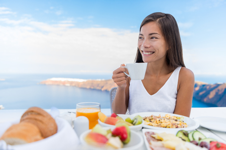 Aziatische Vrouw drinken warme drank in de ochtend ontbijt tafel. Mooie elegante dame met kopje koffie op luxehotel terras met uitzicht op zee in het resort restaurant op Oia eiland Santorini, Griekenland.