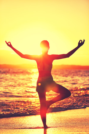 vriksasana: Wellness of mind - Yoga woman standing on one leg doing tree pose with open raised arms in sunset flare doing morning exercise routine on tropical beach. Mindfulness and meditation concept.