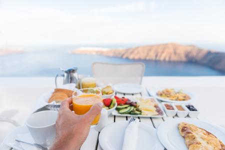 European vacation healthy breakfast food selfie. POV of man drinking morning orange juice at resort restaurant. Table for two on outdoor hotel balcony caldera view on Oia Santorini, Greece, Europe.