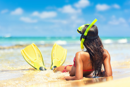 마스크와 핀 해변 휴가 스노클링 여자 스노클링. 스노클링 튜바와 오리발 태양 선탠과 스노클링 후 물에 누워 여름 방학에 편안한 비키니 여자.