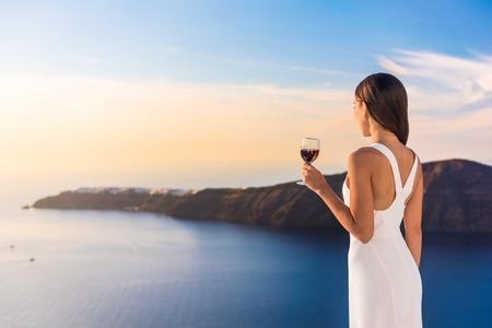 Jeune femme buvant du vin rouge sur la terrasse en regardant belle vue sur le coucher du soleil de la Méditerranée. Femme en sundress blanc sur l'été en Europe vacances Voyage à Santorin, Grèce.