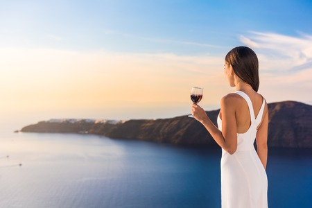 Young woman drinking red wine on outdoor terrace watching beautiful sunset view of Mediterranean Sea. Female in white sundress on summer Europe travel vacation in Santorini, Greece.