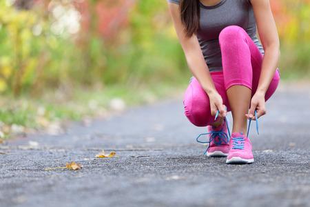 Loopschoenen vrouw runner koppelverkoop schoenkant voor rennen. Close-up van meisje dat klaar voor het aanstoten het rijgen van de kant van de sportschoen wordt. De vrouwelijke agent van de sportfitness in openlucht op bosweg in het seizoen van de de lentedaling.