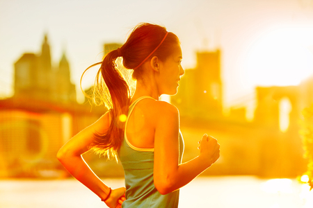 sunset city: Running woman Asian runner in New York city sunset. Runner jogging in sunny bright light. Female fitness model training outside in New York City with skyline and Brooklyn Bridge in background.