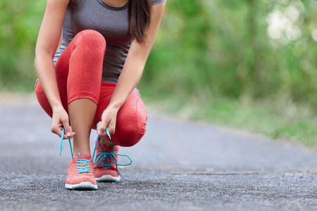 Running shoes - closeup of woman tying shoe laces. Female sport fitness runner getting ready for jogging outdoors on forest path in summer season. Banco de Imagens