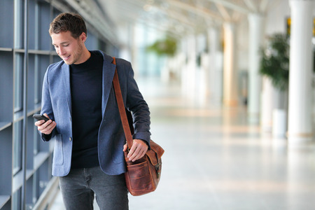 travellers: Business man using mobile phone app in airport. Young business professional man texting smartphone walking inside office building or airport terminal. Handsome man wearing stylish suit jacket indoors.