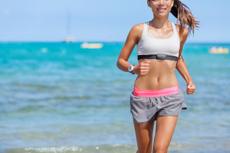 Fitness lifestyle. Runner woman with heart rate monitor running on beach with smartwatch.Fit body fitness athlete training cardio working out outside in summer, healthy living health concept.