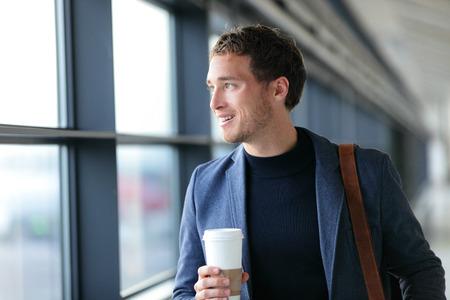 행복 한 사업가 마시는 커피 - 여행 라이프 스타일이나 아침 통근 도시 생활을하려고합니다. 사무실 builing 또는 공항 터미널에서 창 근처 젊은 전문 남