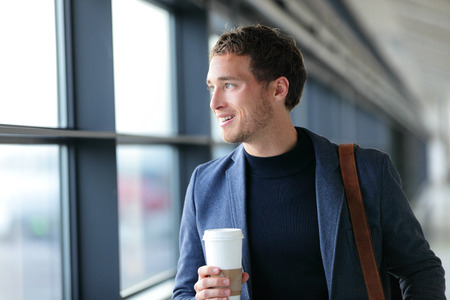 Happy businessman going to work drinking coffee - travel lifestyle or morning commute urban living. Young professional man near window in office builing or at airport terminal business class flight. Banco de Imagens
