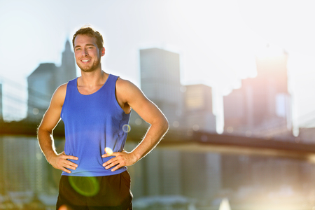 outdoor outside: Sport athlete man running portrait in New York City - Brooklyn Bridge and Manhattan skyline in background. Active healthy lifestyle fit fitness runner outside training fitness workout outdoor in NYC.