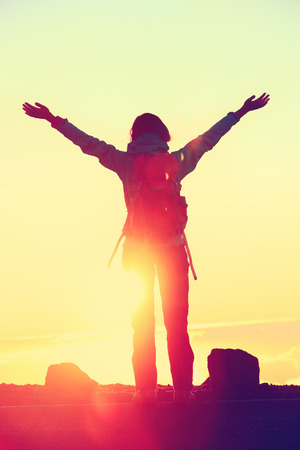 top mountain: Happy hiker freedom having reached summit goal with success at sunset. Silhouette of woman with backpack celebrating winning standing at mountain top with arms up in celebration during hiking travel. Stock Photo