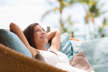 Home lifestyle woman relaxing enjoying luxury sofa patio furniture on outdoor patio living room. Happy lady lying down on comfortable pillows daydreaming thinking. Beautiful young Asian chinese girl.